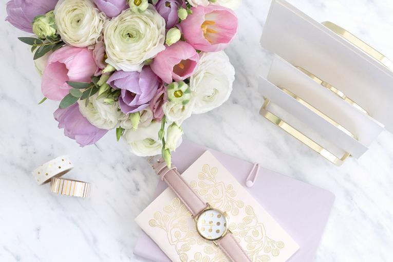 Çiçek ve saat masanın üstünde duruyor.